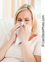 Portrait of an ill woman blowing her nose in her living room