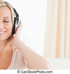 Close up of a lovely woman listening to music with her eyes...