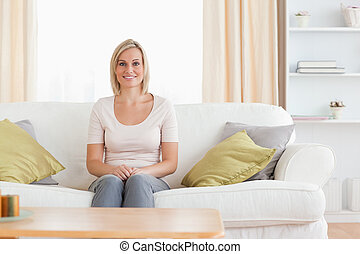 Cute woman sitting on a sofa in her living room