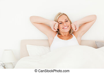 Woman stretching her arms in her bedroom
