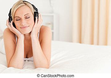 Delighted woman wearing headphones in her bedroom
