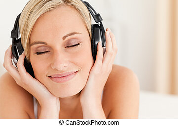 Close up of a delighted woman wearing headphones in her...