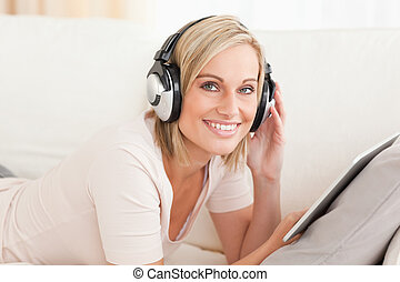 Woman with a tablet computer and headphones looking at the...