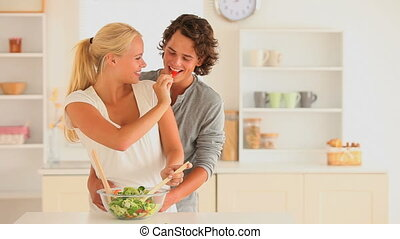 Happy couple preparing thier salad