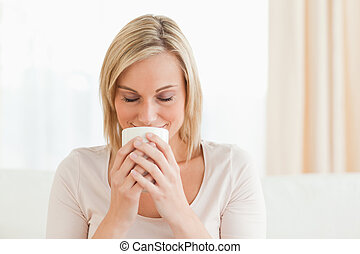 Smiling woman smelling her cup of coffee with her eyes...