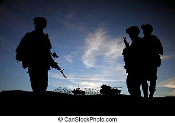 Modern day soldiers in Middle East silhouette against sunset...