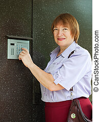 Mature woman dialing an intercom to enter a building