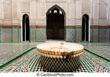 Ornate tiles and fountain in a madrasa - Meknes, Morocco:...