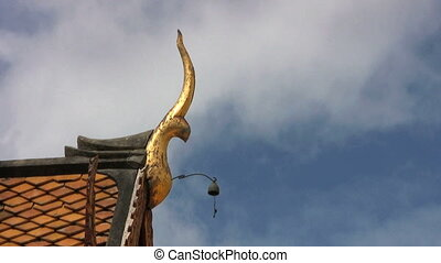 Temple Roof With Bell - A Buddhist temple with a golden...