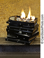 burning stack of hard drives in rusty background. the top...