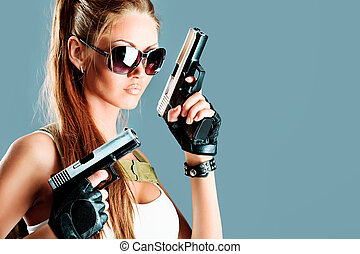 war - Shot of a sexy military woman posing with guns