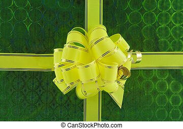 yellow holiday bow on green background