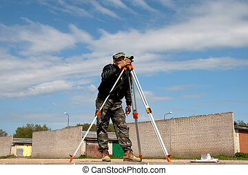 Theodolite on a tripod with construction worker