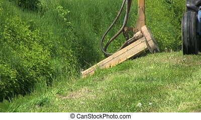 Tractor Cutting Grass In Ditch - A close up shot of a farmer...