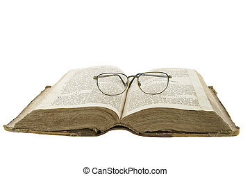 Vintage open book bible open and glasses on it isolated over white