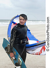 Kite surfer wearing a wetsuit on the beach on a windy day,...