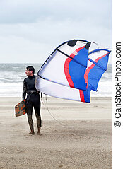 Kite Surfer - Kite surfer wearing a wetsuit on the beach on...