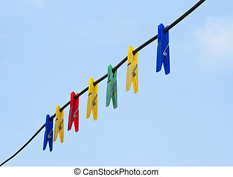 Colorful clothes pegs hanging in the line wire over blue sky