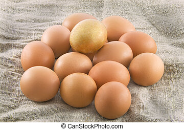 One golden egg with many ordinary fresh rural eggs lying on...