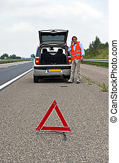 Broken down car at the side of the road, with a man, wearing...