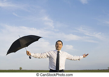 Happy businessman standing with umbrella in the meadow