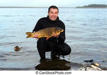 A young man scuba diver spear fish a carp