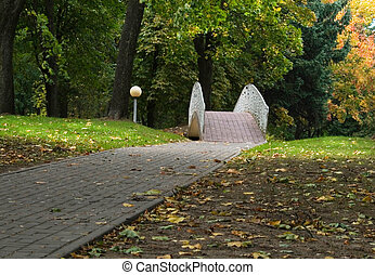 alley and  bridge in park at autumn day