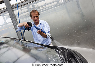 Car wash - Man washing the windscreen of his car in a...
