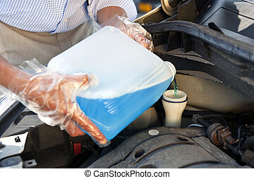 Refilling windscreen wiper fluid - Man wearing plastic...