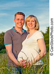 Pregnant couple in the park - Happy pregnant couple in the...