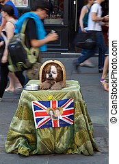 Beggar with a poster of Kate and William - Beggar dressed as...