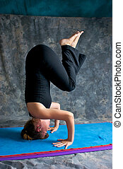 young woman doing advanced yoga asana Sirsasana or Headstand...