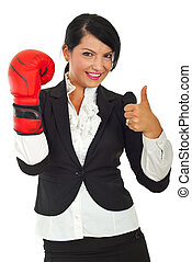 Successful business woman with boxing glove giving thumb up...