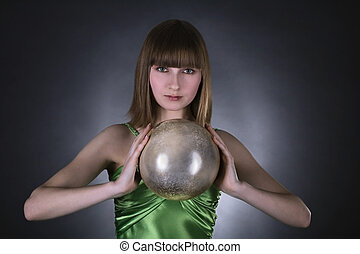 stunning woman in green dress with gold sphere in hand over...