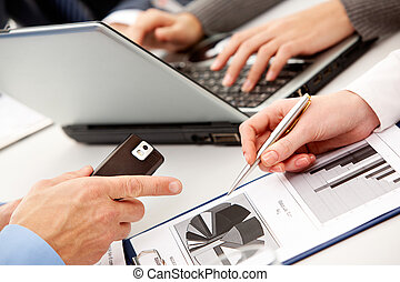 Pointing at diagram - Above view of business people hands...