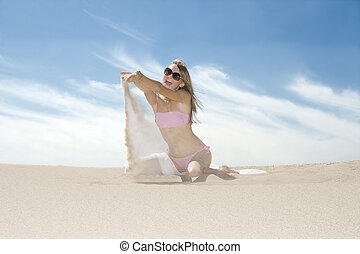 Young emotional woman pouring sand from her hands