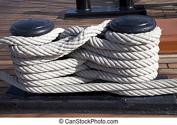 Old ropes around mooring bollard in a deck
