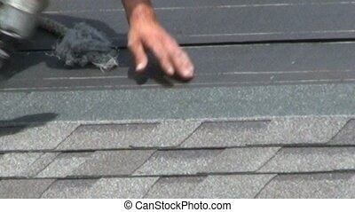 Roofing A House - A man uses a nail gun to lay shingles on...