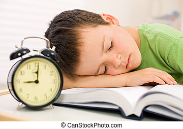 Past bedtime for little schoolboy - asleep on his book