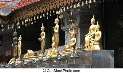 Small Buddha Statues - A row of small Buddha statues at a...
