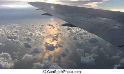 Sunset From Airplane - Clouds float above the ocean as the...