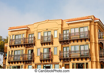Stucco Hotel with Iron Window Coverings - A yellow stucoo...