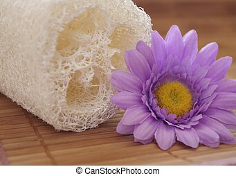 loofah and flower on bamboo background