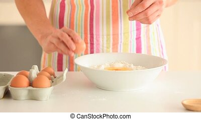 Close up of feminine hands baking while wearing an apron