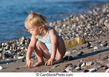 Beautiful baby girl sitting on the beach at the seashore