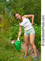 Young woman in kitchen-garden - Young woman holding watering...