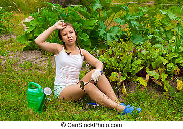 Young woman in kitchen-garden - Young woman sitting on...