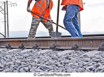 railway embankment, rails and workers in orange vests