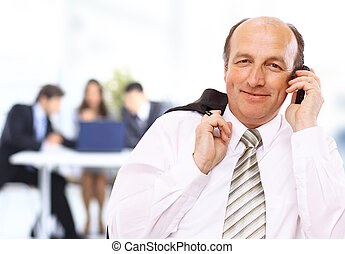 Smiling business man using cellphone with colleagues in blurred background