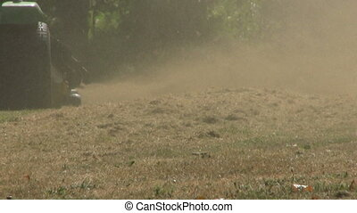 Riding Lawn Mower Blowing Brown Gra - A man on a riding lawn...